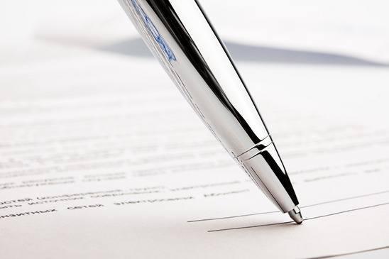 en sølvkuglepen skal til at skrive på en kontrakt